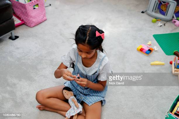 young girl sitting crossed legged with doll in lap - bow legged stock photos and pictures