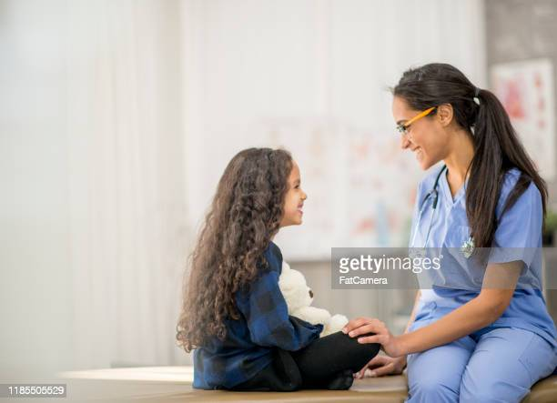 young girl sitting cross-legged face to face with nurse stock photo - pediatrician stock pictures, royalty-free photos & images