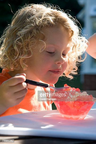Young girl sitting in a backyard eating jello