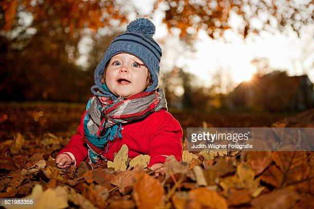 Young girl sitting in autumn leaves