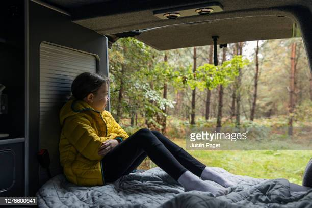 young girl sitting in back of campervan. - non urban scene stock pictures, royalty-free photos & images