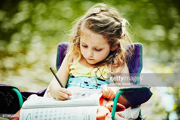 Young girl sitting in chair while camping coloring