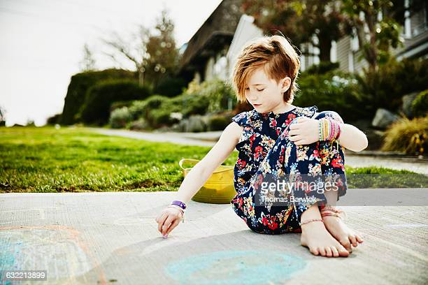 Young girl sitting in driveway drawing with chalk
