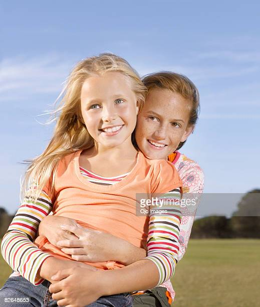 young girl sitting in friend's lap - alleen meisjes stockfoto's en -beelden