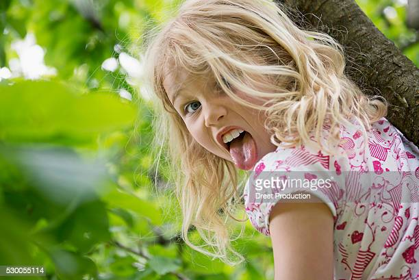 young girl sitting in tree sticking tongue out - little girl sticking out tongue stock photos and pictures