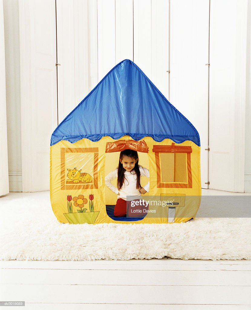 Young Girl Sitting Inside a House-Shaped Tent : Stock Photo
