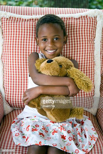 Young girl sitting on a couch hugs a toy dog, KwaZulu Natal Province, South Africa