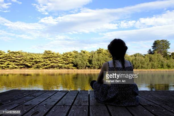 young girl sitting on a jetty looking at calm nature landscape view - rafael ben ari stock-fotos und bilder