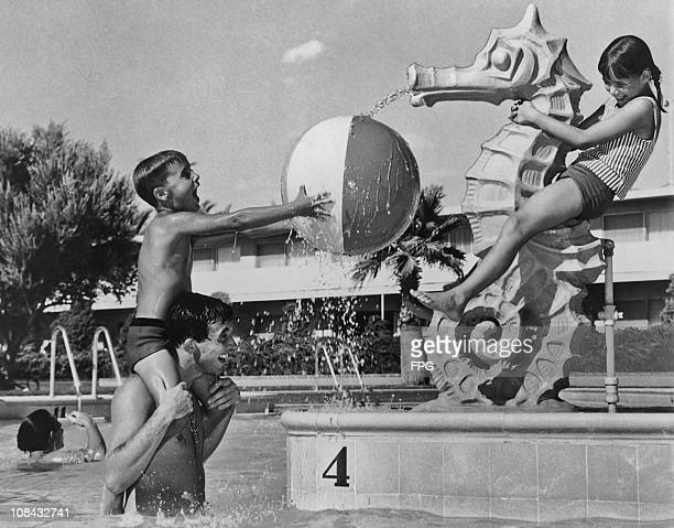A young girl sitting on a seahorse water feature plays with her brother and father in a swimming pool circa 1950