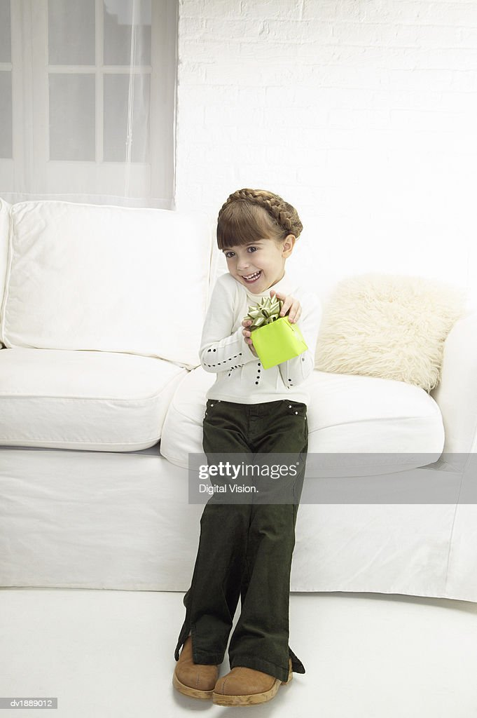 Admirable Young Girl Sitting On A White Sofa Holding A Wrapped Gift Squirreltailoven Fun Painted Chair Ideas Images Squirreltailovenorg