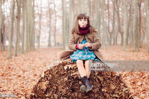 Young girl sitting on autum leaves ball