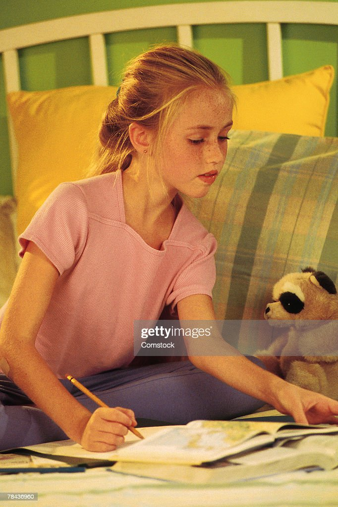 Young girl sitting on bed doing homework : Stockfoto