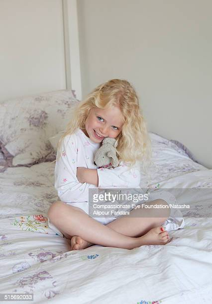 Young girl sitting on bed hugging teddy