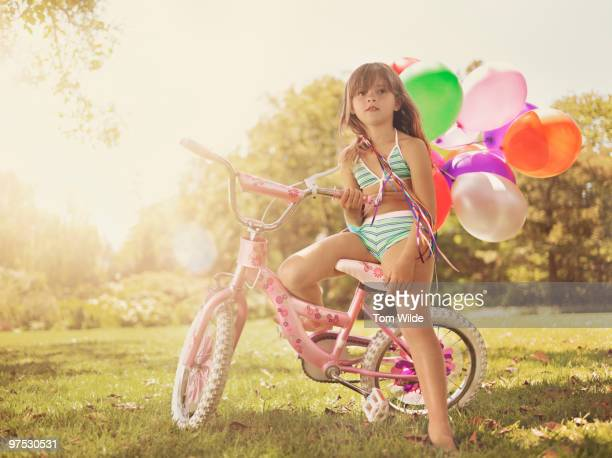 young girl sitting on bike with balloons