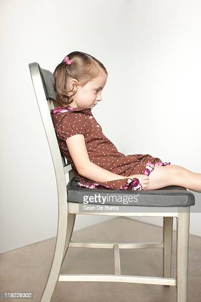 Young girl sitting on chair.