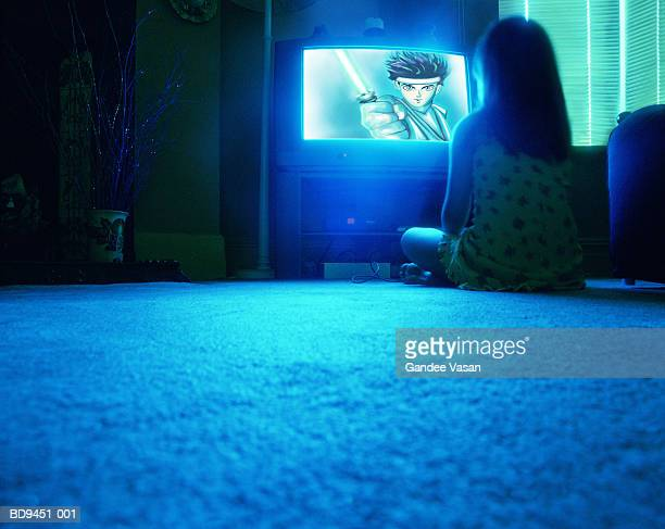 Young girl (8-10) sitting on floor watching television, rear view