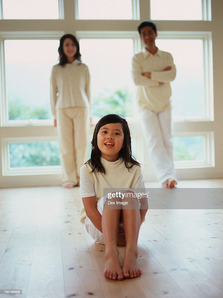 Young girl sitting on ground, parents standing in background : Stock Photo