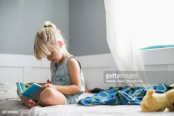 Young girl sitting on her bed reading a childrens Bible