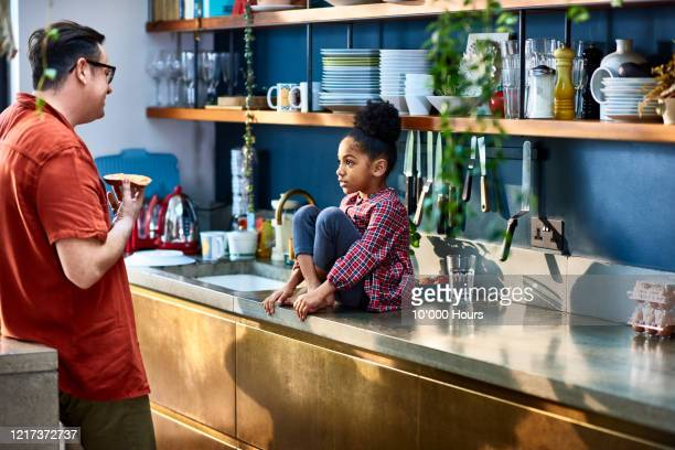 young girl sitting on kitchen counter talking to father - talking stock pictures, royalty-free photos & images