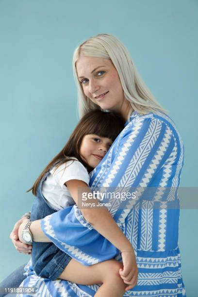 young girl sitting on mothers lap against pale blue background - nerys jones stock photos and pictures
