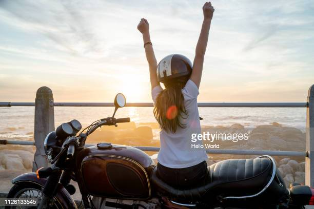 young girl sitting on retro motorcycle showing victory with arms - cheio imagens e fotografias de stock