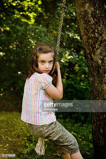 Young girl sitting on rope swing, portrait