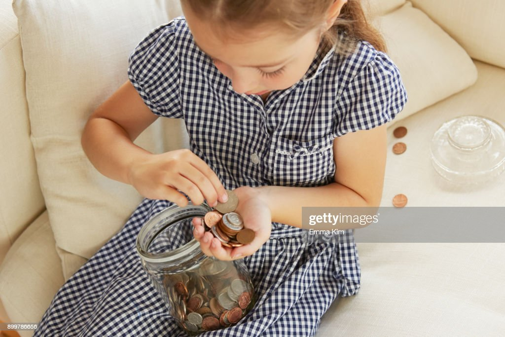 Young girl, sitting on sofa, counting money from jar, elevated view : ストックフォト