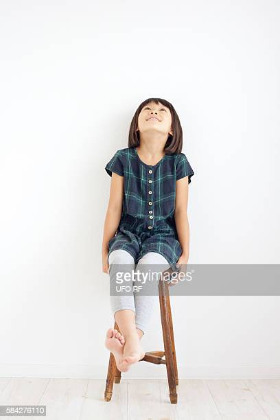 Young Girl Sitting on Stool and Looking Up