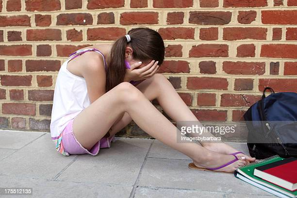 young girl sitting on the floor upset after being bullied - alleen één tienermeisje stockfoto's en -beelden