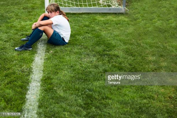 young girl sitting on the grass after a match defeat. - sideline stock pictures, royalty-free photos & images