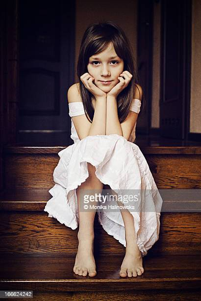 A young girl sitting on the wooden stairs