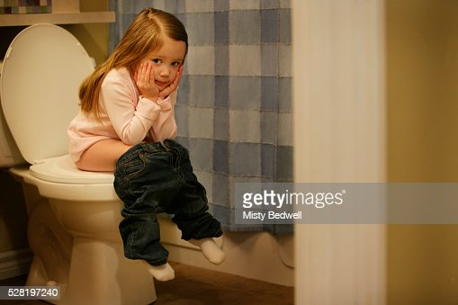 Young Girl Sitting On Toilet Stock Photo | Getty Images