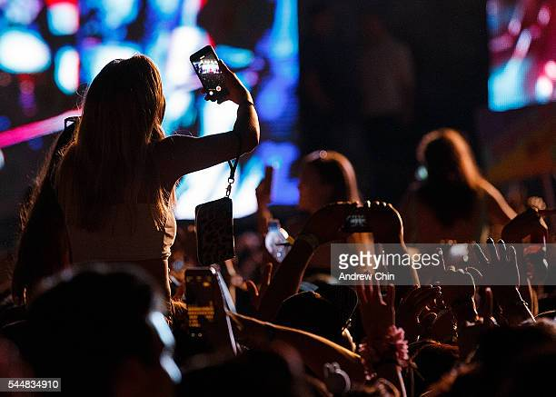A young girl sitting ontop of her partner's shoulders uses her mobile phone to record Zedd's performance onstage during day 2 of FVDED In The Park at...