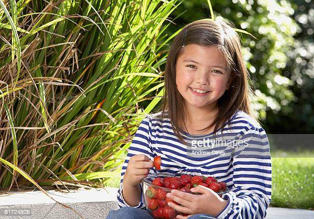 young girl sitting outdoors with a bowl of strawberries smiling - 8 9 años fotografías e imágenes de stock
