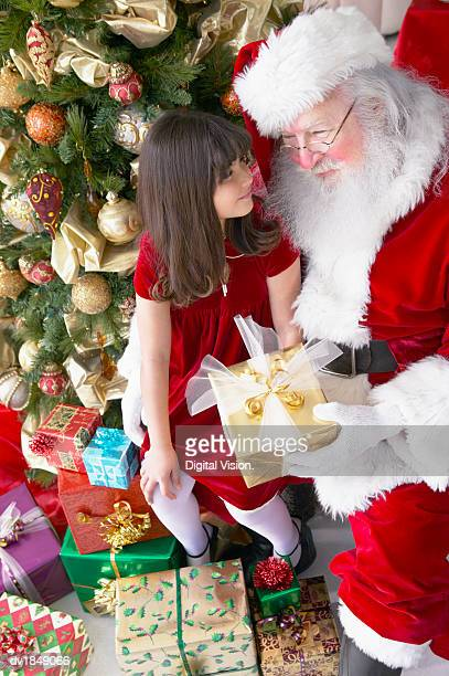 Young Girl Sitting With Santa Claus by a Christmas Tree