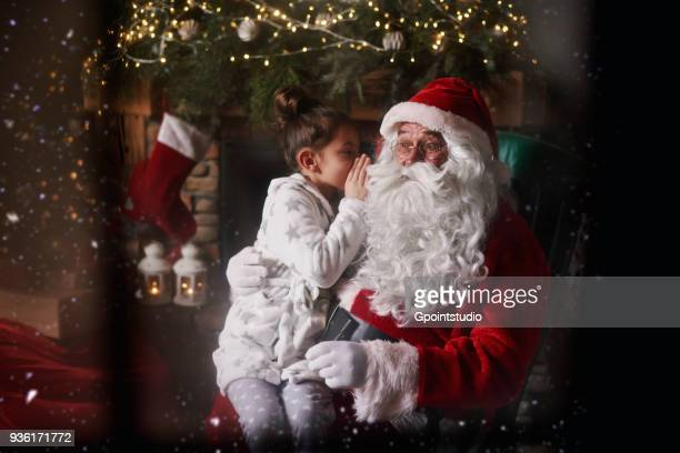 young girl sitting with santa, whispering into santas ear - grotto stock pictures, royalty-free photos & images