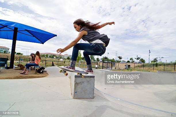 Young girl skateboarder doing a trick in a skate park. She has brown hair and eyes and is wearing blue jeans and a short sleeved sweater top.