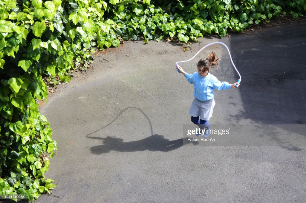 Young Girl Skipping on a Rope at Home Back Yard : Stock Photo