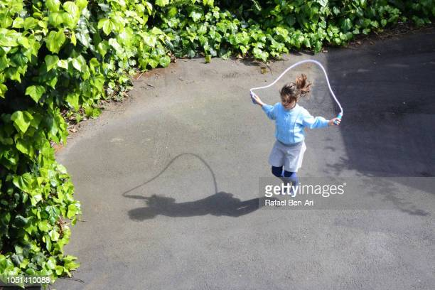 Young Girl Skipping on a Rope at Home Back Yard