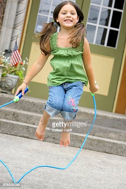 young girl skipping rope - skipping along stock-fotos und bilder