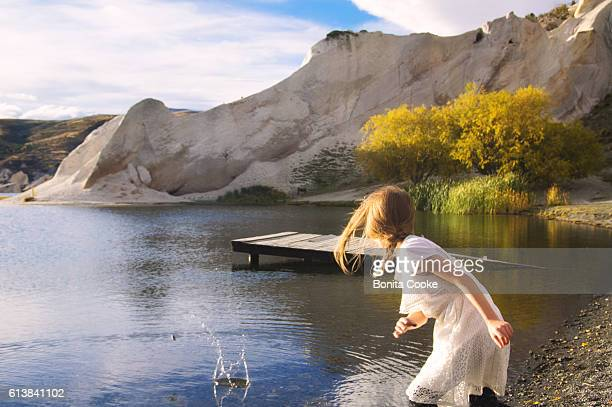 Young girl skipping stones at Blue Lake, St Bathans, Central Otago