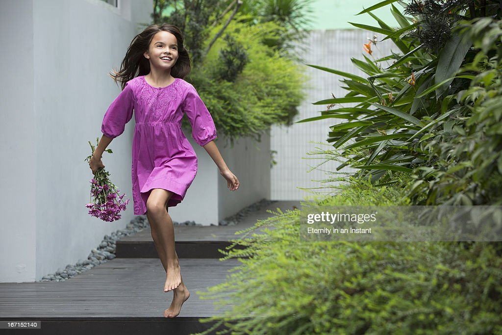 Young girl skipping whilst holding flowers : Stock Photo