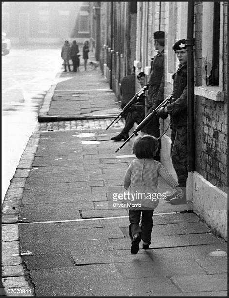 A young girl skips past patrolling British soldiers from the Gloucester Regiment who had become an every day reality to her Belfast Northern Ireland...