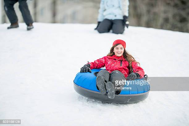 Young Girl Sledding Down a Hill