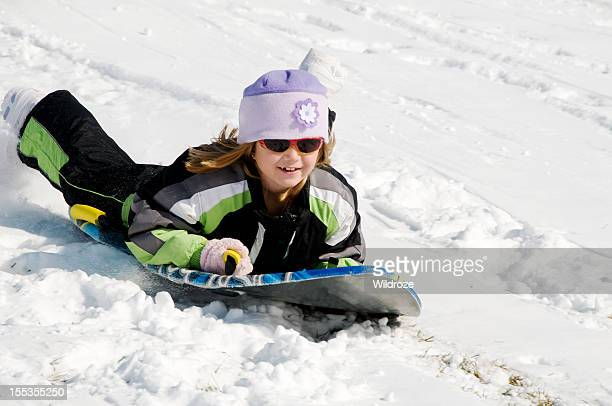 young girl sleds down snow covered hill - tobogganing stock pictures, royalty-free photos & images