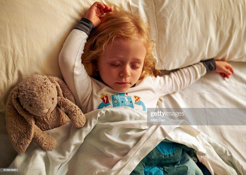 Young girl sleepign with stuffed rabbit : Stock Photo
