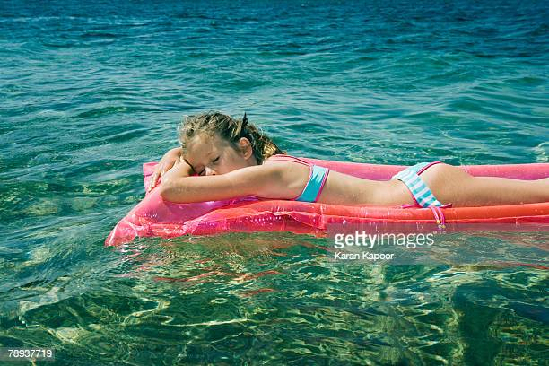 young girl sleeping floating on an inflatable raft. - little girl laying on the beach stock photos and pictures