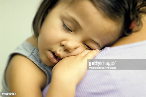 A young girl sleeping on a persons shoulder