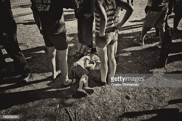 A young girl sleeps as US President Barack Obama delivers remarks during a campaign event at Herman Park in Boone Iowa on August 13 2012