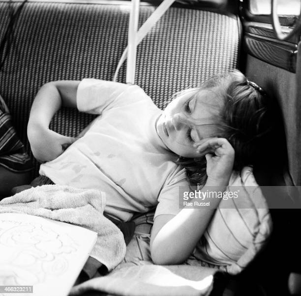 A young girl sleeps in the backseat of an automobile during a drive back from a trip to Washington DC 1949